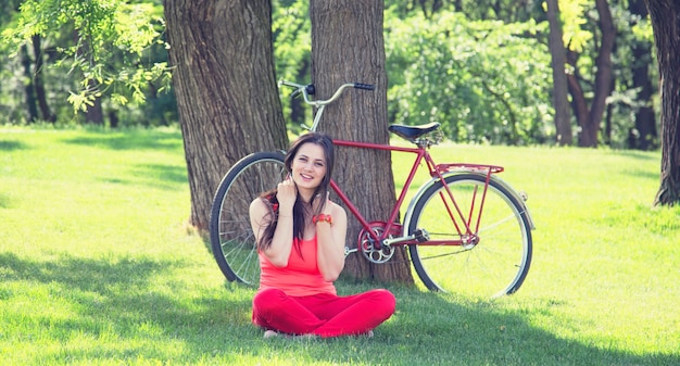 Brunette girl with cup of coffee in the park and with bicycle on surface.