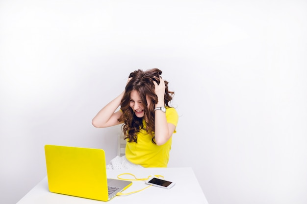 A brunette girl with curly hair is playing silly in front of a laptop in yellow case.