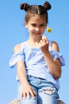 青い空を背景に彼女の手にタンポポを持つブルネットの少女。高品質の写真