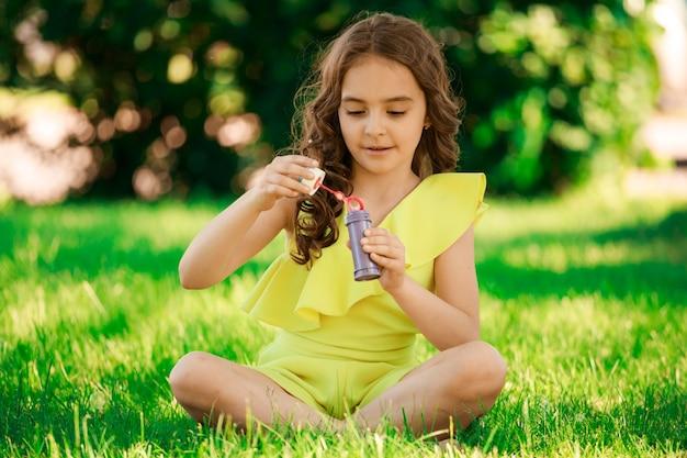 Девушка брюнетка с темными волосами сидит на траве в парке и пускает мыльные пузыри. детский портрет. счастливое детство. фото высокого качества