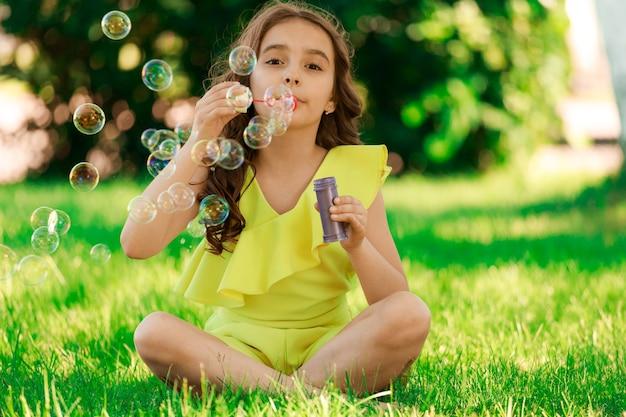 Девушка брюнетка с темными волосами сидит на траве в парке и пускает мыльные пузыри. фото высокого качества