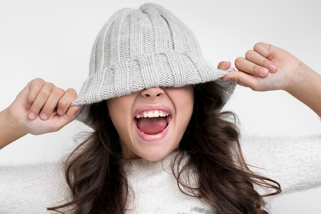 Brunette girl with the hat on her eyes screaming