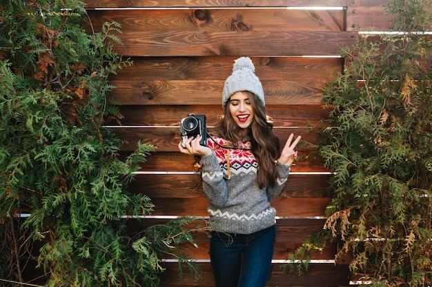 Ragazza castana con capelli lunghi in vestiti di inverno divertendosi con la macchina fotografica nelle mani sui rami verdi circondano all'aperto di legno