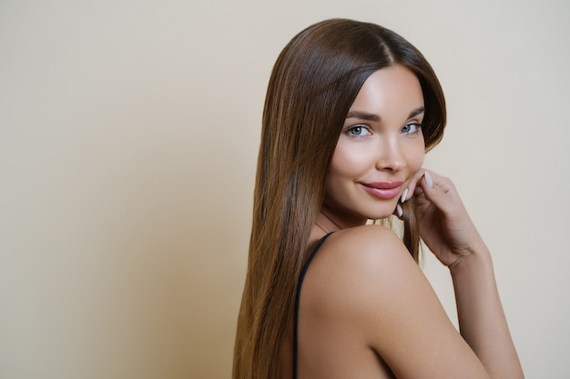 Brunette girl with long shiny hair, glowing healthy skin, manicure and makeup
