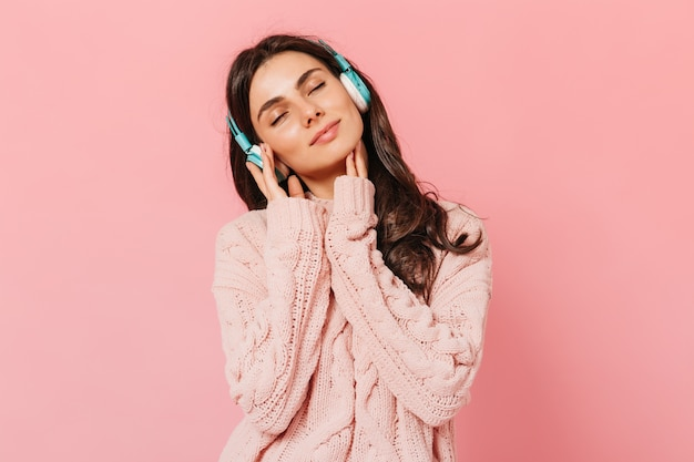 Brunette girl with pleasure listens to music on headphones. woman in pink outfit smiling on isolated background.