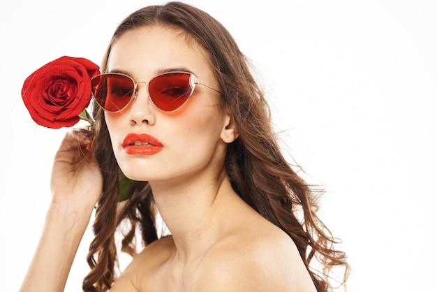 赤いバラとサングラスの裸の肩を持つブルネットの少女。高品質の写真