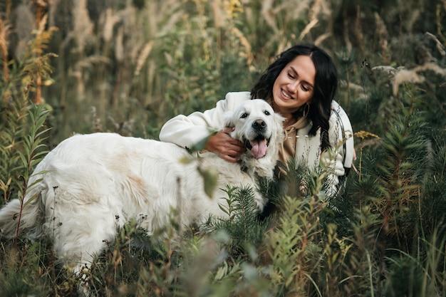 フィールドで白いゴールデンレトリバー犬とブルネットの女の子