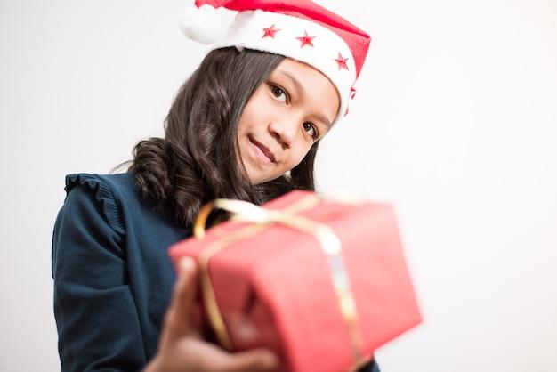 빨간색 선물을 들고 흰색 바탕에 카메라를 찾고 크리스마스 모자와 갈색 머리 소녀.