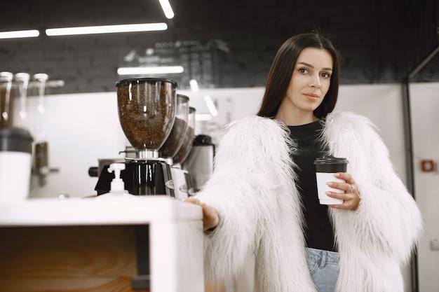 갈색 머리 소녀. 백색 모피 코트에있는 여자. 카운터에서 소녀.