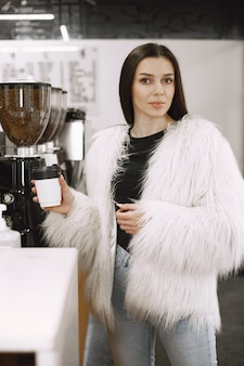 Brunette girl. woman in a white fur coat. girl at  counter.