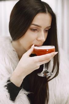 Ragazza bruna. donna in una pelliccia bianca. cocktail rosso