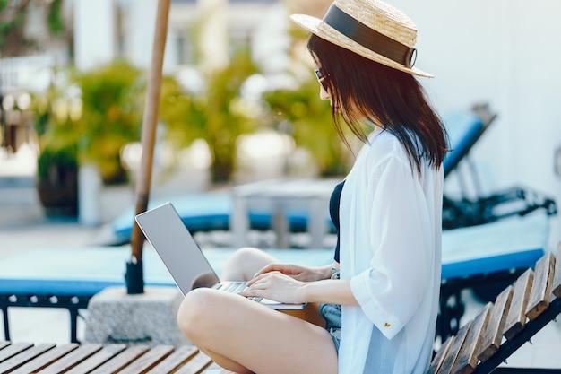 갈색 머리 소녀는 수영장에서 그녀의 컴퓨터에서 작업