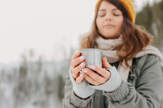 Brunette girl in yellow knitted hat with metal mug of hot tea in the forest outdoors in winter, selective focus