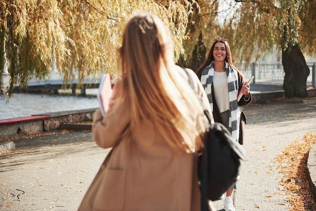 Брюнетка идет и улыбается. двое молодых друзей рады встретиться в парке после учебы