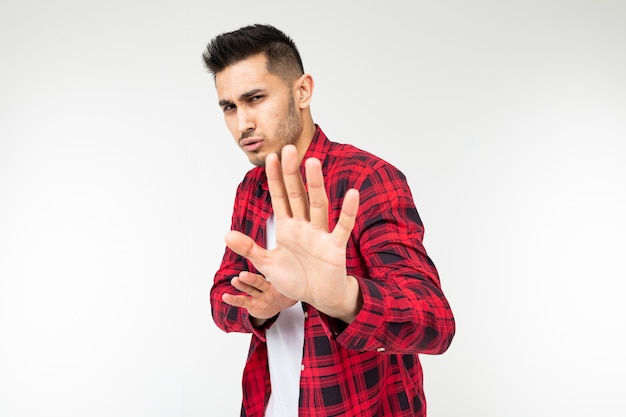 Brunette guy in a checkered shirt swinging open hand wave on a white studio background