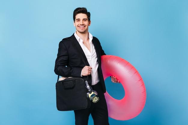 Ragazzo brunetta in abito classico sorride e posa con maschera subacquea e anello di gomma rosa.