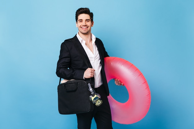 古典的なスーツのブルネットの男は、ダイビングマスクとピンクのゴムリングで笑顔とポーズをとっています。