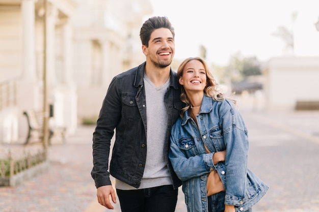 Brunette guy walking with girlfriend in weekend. outdoor portrait of happy young people enjoying date.