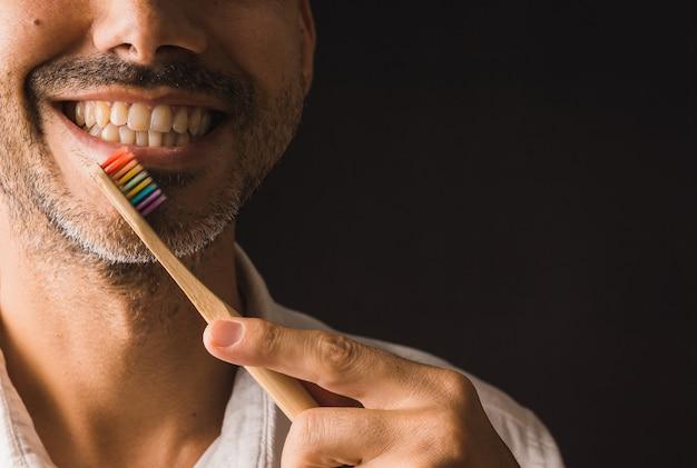 Брюнетка с бородой улыбается с радужной зубной щеткой в левой части изображения на черной стене