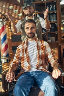 Brunette hair-stylist holding hands up while his client is sitting in an armchair at a barbershop