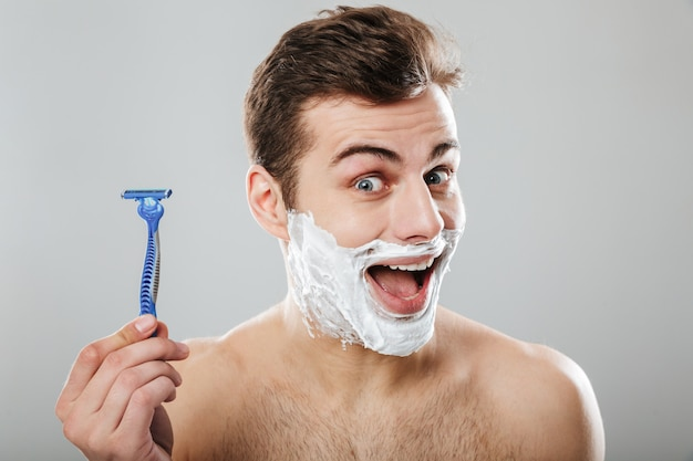 Brunette happy guy 30s being undressed at bathroom with shaving cream on face holding razor in hand over grey wall
