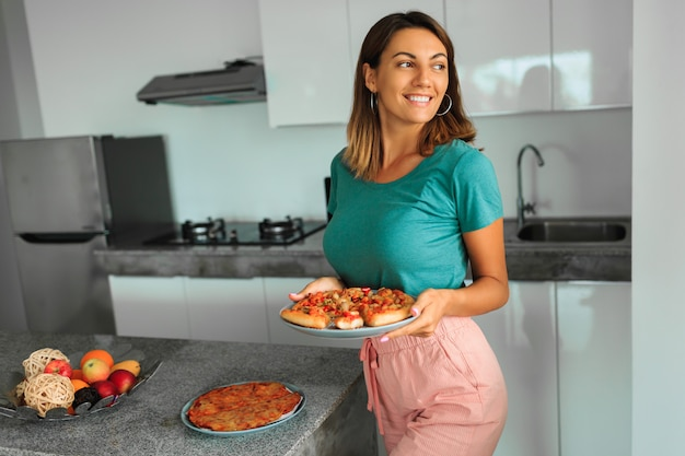 Brunette happy woman holding plate with pizza on kitchen in modern house