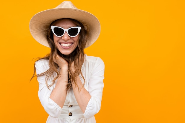 Brunette in a hat and sunglasses on a  of a yellow wall, half-length portrait