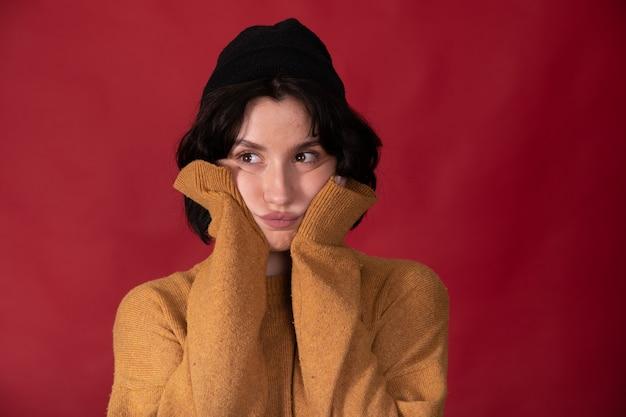 Брюнетка-хипстер девушка в горчичном свитере держит руками за щеки в рукавах