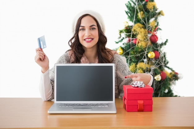 Brunette holding credit card and showing her laptop