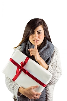 Brunette holding gift and keeping a secret