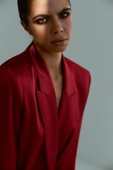 彼女の頭の上に彼女の手を保持しているブルネット赤いジャケットファッションスタジオの装飾