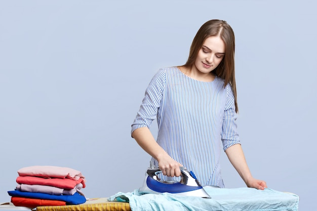 Brunette housewife irons clothes on ironing boards, peals it neatly, being busy all day long, does domestic work, isolated on blue. woman with electric iron. housework concept