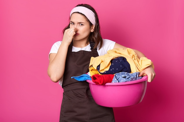 Brunette houseworker holding her nose with one hand, having full pink basin of bad smelling items of clothes, trying to bear smell. emotional exhausted model poses isolated over pink wall.