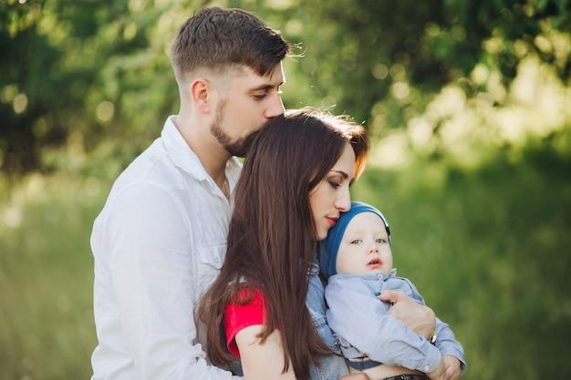 Брюнетка муж целует свою жену, женщина держит маленького сына и обнимает