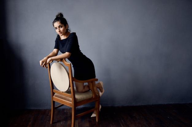 椅子の近くの黒いドレスを着たブルネット高級ファッションライフスタイルスタジオ