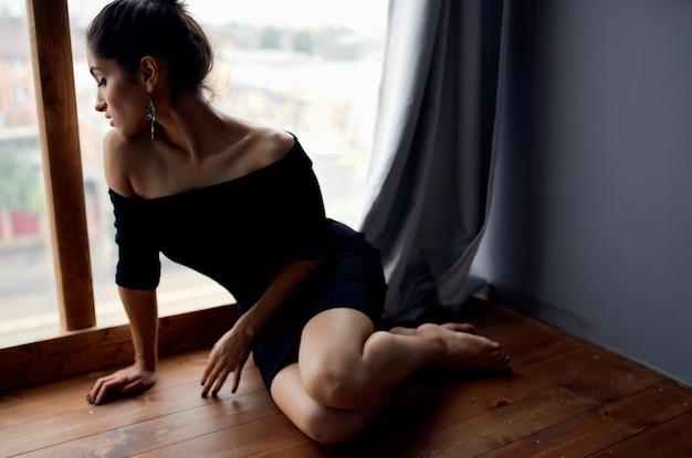 ファッションモデルのポーズをとる窓の近くの黒いドレスのブルネット