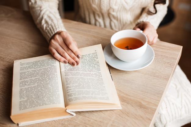 Брюнетка в кафе пьет чай, ест сладкое, читает книгу, вьющиеся волосы. отдыхаете после дня, полного удовольствия от жизни. мягкие теплые тона.