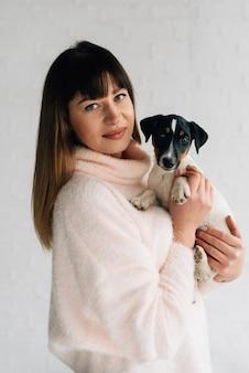 軽いニットのセーターを着たブルネットがペットを抱き、カメラを覗き込む、子犬のラッセルテリア