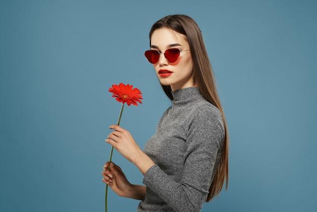 赤い花のブルネットは暗いメガネの青い背景を回復します
