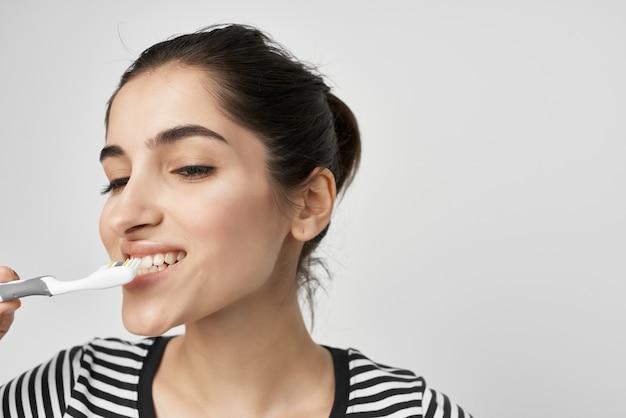 Брюнетка в полосатой футболке чистит зубы крупным планом