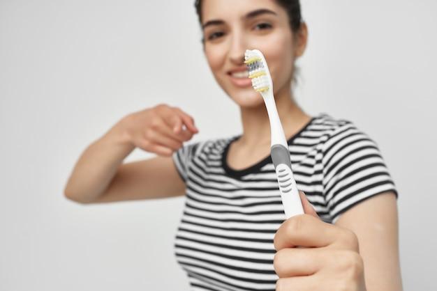 手の光の背景に縞模様のtシャツの歯ブラシでブルネット Premium写真