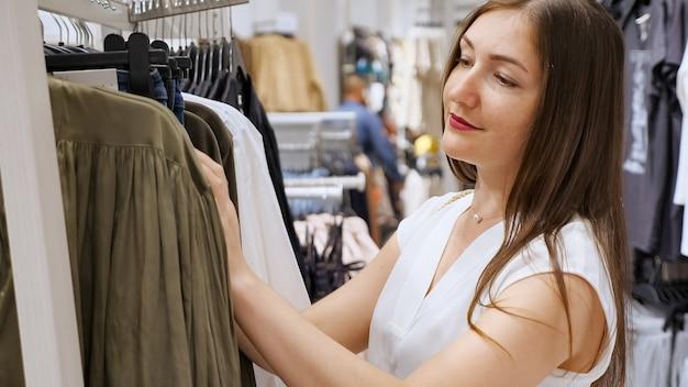 白い半袖ブラウスのブルネットは店でシャツを選びます。