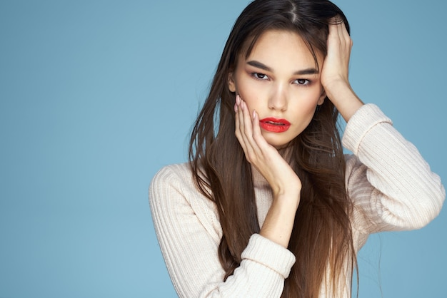 白いセーターの赤い唇の魅力の長い髪の青い背景のブルネット