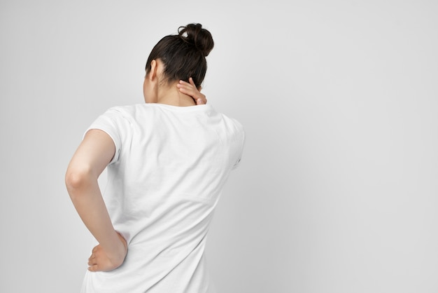 首の明るい背景の白いtシャツの痛みでブルネット。高品質の写真