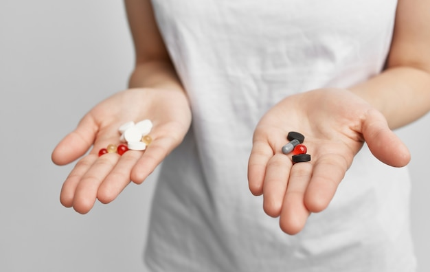 Брюнетка в белой футболке с таблетками в руках, проблемы со здоровьем
