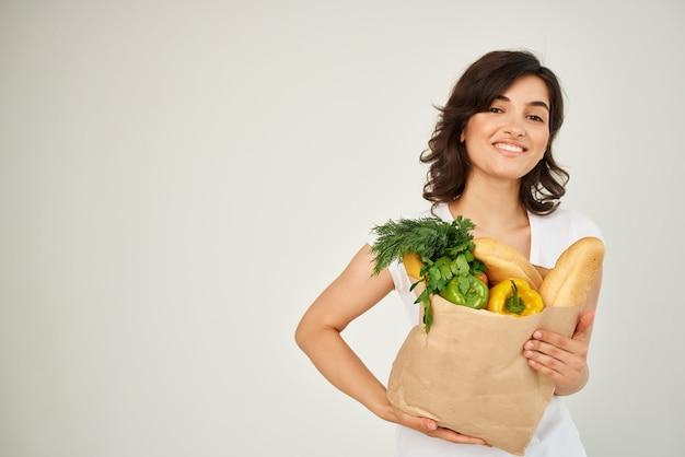 白いtシャツのブルネットは、食品野菜の配達をパックします
