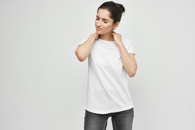 Брюнетка в белой футболке с болью в шее на светлом фоне
