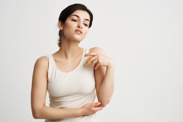 彼女の手にスポンジを持った白いtシャツのブルネットはスキンケア化粧品に直面しています