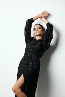 Брюнетка в черном платье держит руки над головой очарование моды