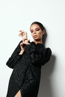 壁のモデルに寄りかかってポーズをとる黒いドレスのブルネット